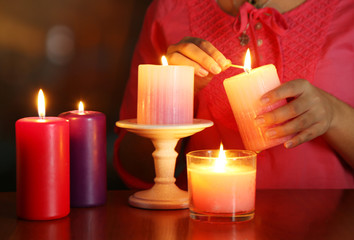 Woman lights candles on bright background