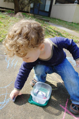 Child Drawing with Chalk Outside