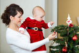 mother  and baby girl decorating Christmas tree at home