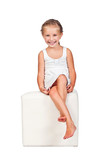 Little girl on a white cube isolated on a white background