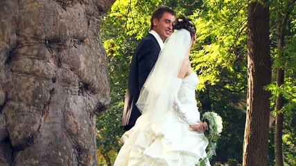 Newlyweds walking hand in hand in a park