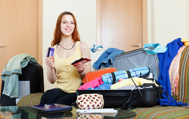 woman sitting on sofa and packing suitcase