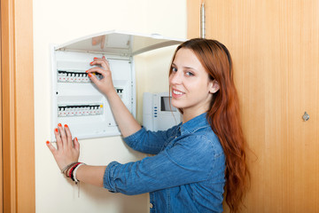 Long-haired woman turning off the light-switch at power control