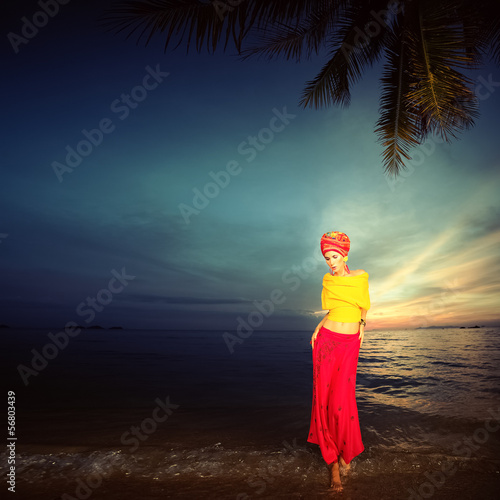 Sensual girl in oriental style on the beach at sunset