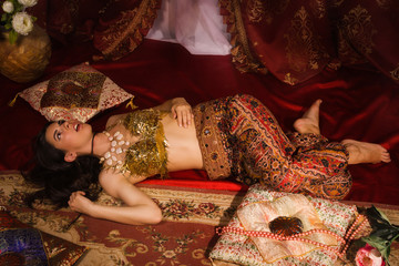 Crime scene imitation: lifeless woman in oriental costume lying