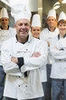 Five chefs wearing uniforms while posing in a kitchen