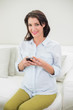 Pleased pregnant brown haired woman using her mobile phone