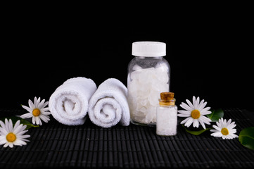 flowers and towel, salt in glass, zen stone on mat