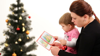 Mother reading a Christmas story to her little daughter