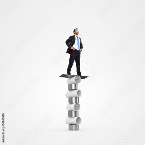 businessman balancing on circus cylinders