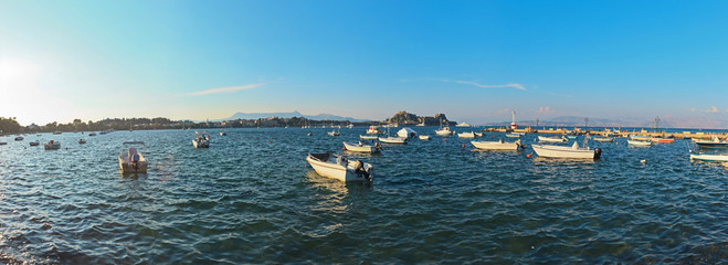 Panoramic shot of sea with boats in Corfu city. Blue sky. Kerkir