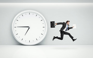 large wall clock and running businessman