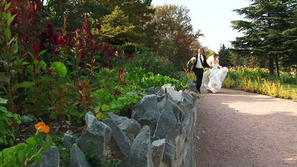 Newlyweds running along a path in a park