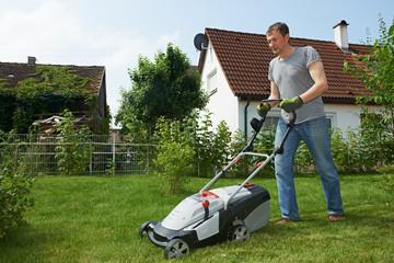 man mowing lawn in backyard