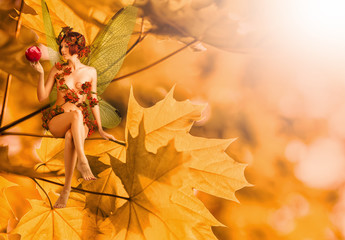 autumn fairy with wings sitting on orange leaves