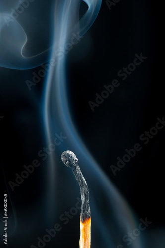 burnt match with smoke, black background
