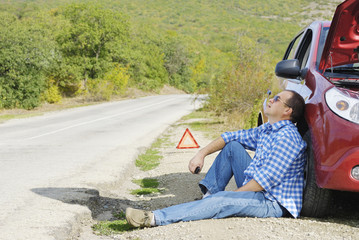 Adult man is sitting near his broken car