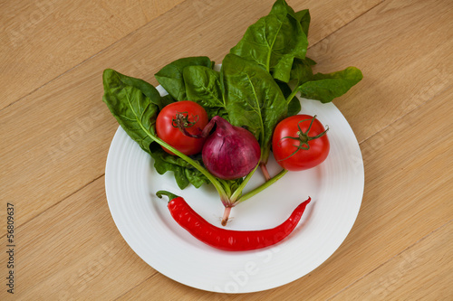 Vegetable face on a white plate
