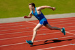 Young caucasian athlete sprinting on track