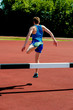 Athlete jumping over the hurdle