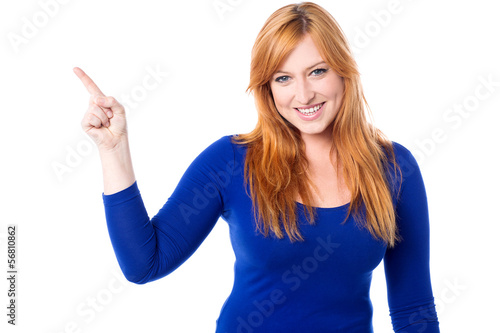 Young woman pointing away over white