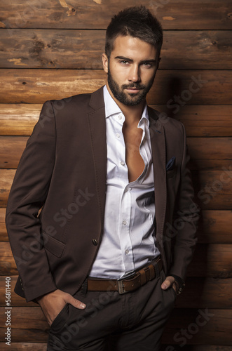 Young beautiful fashionable man against wooden wall.