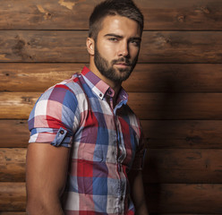 Portrait of young beautiful man against wooden wall.