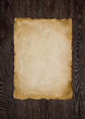 Old paper sheet on brown wooden background