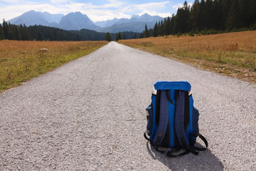 Backpack on the road leading into the mountains