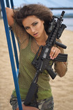 Girl with a rifle on the beach