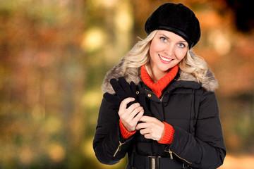 Blonde Frau mit Mütze und Handschuhen in der Hand