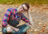 Hipster sitting in the autumn park