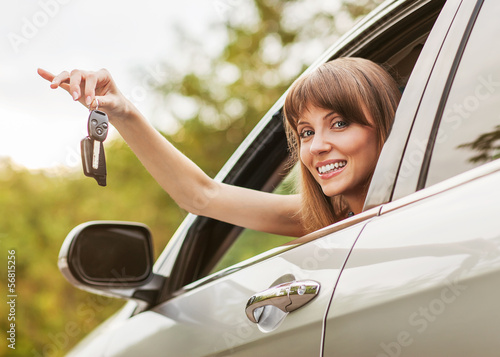 Caucasian car driver woman smiling showing new car keys and car.