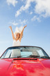 Happy woman standing in cabriolet while her boyfriend driving