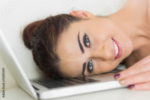 Young smiling woman lying her head on a laptop