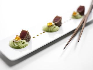Thunfisch gewürzt mit schwarzem Pfeffer mit Gurken und Sesam