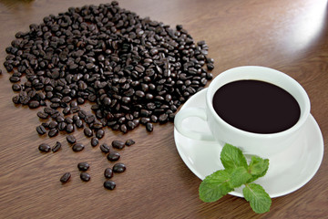 Coffee beans and green peppermint near a white coffee cup.