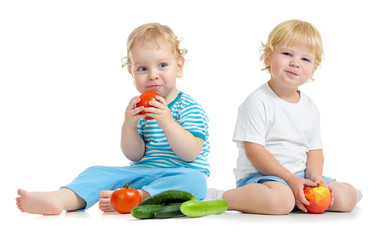 Two happy kids eating healthy food fruits and vegetables