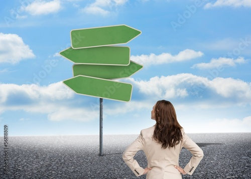 Businesswoman standing back to camera looking at road signs