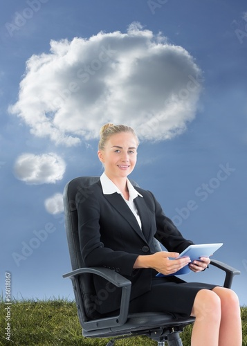 Blonde businesswoman sitting on swivel chair with tablet
