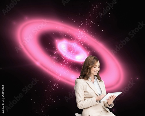 Pleased businesswoman using a tablet pc sitting on chair