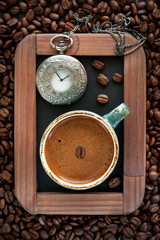 Сup of coffee and a vintage pocket watch on a chalkboard
