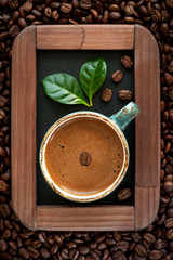 Сup of coffee with green leaves on a chalkboard