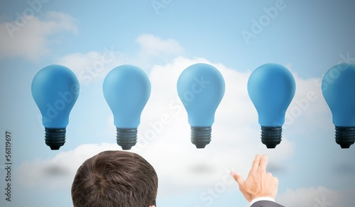 Businessman pointing with two fingers at blue light bulbs