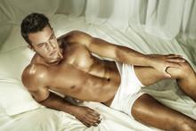 Przystojny nagi mężczyzna leżał w łóżku.