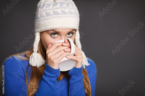 Winter woman wearing warm clothing drinking tea