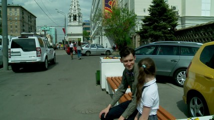 Dad and daughter talking on a bench at the Moscow city street
