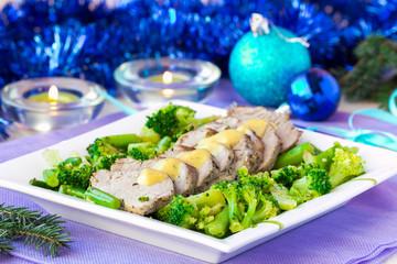 Baked, sliced fillet of pork with green vegetables, broccoli
