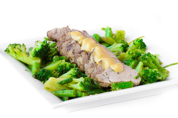 Baked, sliced fillet of pork with green vegetables, broccoli