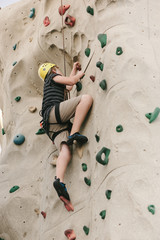 A boy climbing on a rock wall.
